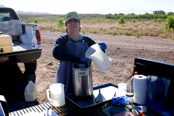 Image of ...Marisa Thompson Mixing Chemical Treatments (Photo by 2009 Weed Science Field Crew)